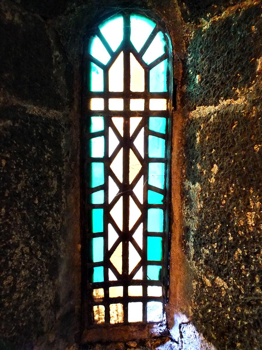Kleines Buntglasfenster mit herausgebrochenen Teil unten rechts