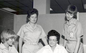 Altes Foto von vier Frauen in Schwesternkittel, die sich gemeinsam Unterlagen ansehen