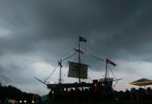 Ein Bierstand in Form eines großen Segelboots gegen das Licht vor heraufziehendem Unwetter.