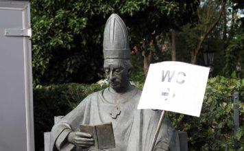 """Eine Statue eines Bischoffs. Auf den Bischoffsstab wurde ein Wegweise """"WC"""" angebracht."""