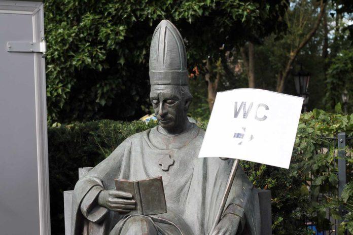 Eine Statue eines Bischoffs. Auf den Bischoffsstab wurde ein Wegweise