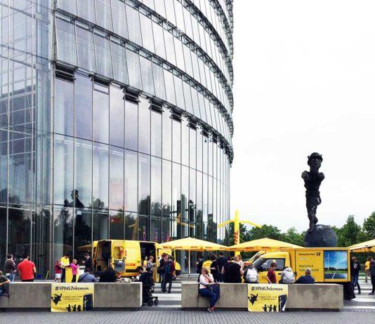 Gelbe Postwagen, gelbe Schirme und als Pikachu gelb verkleidete Menschen stehen am Fuße des Post Towers.