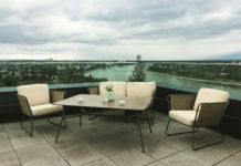 Zwei Sessel und ein zweisitziges Sofa stehen in der Ecke einer Terrasse auf dem 17. Stock. Im Hintergrund sieht man den Rhein fließen.