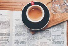 Eine aufgeschlagene Zeitung, auf der eine Tasse Espresso und ein Glas Wasser steht