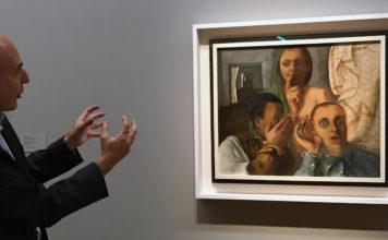 Ein Mann steht gestikulierend vor einem Bild.