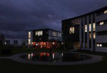 Zwei Glasgebäude bei relativer Dunkelheit, einzelne Lichter brennen, im linken Gebäude farbig. Davor ein kleiner Teich, in dem sich die Lichter spiegeln.