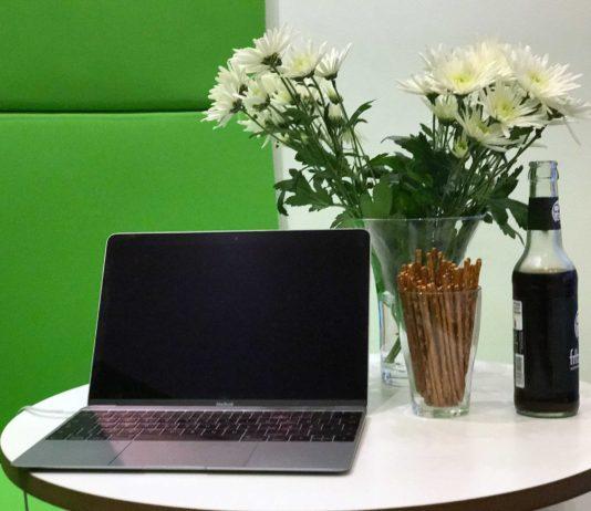 Ein runder kleiner Tisch, darauf ein Laptop, eine Blumenvase, ein Glas mit Salzletten und eine Flasche Fritz-Cola.