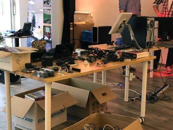 Ein Tisch im Vordergrund, andere im Hintergrund. Darauf viele technische Geräte, Monitore, Kabel. Darunter Kartons mit weiterem Material.