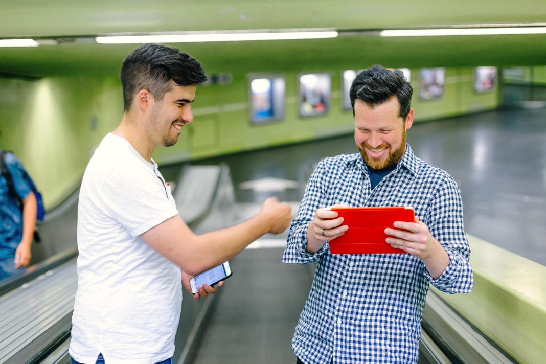 Sascha und Johannes stehen auf einer Rolltreppe. Johannes hält ein iPad in der Hand, Sascha boxt ihn (hoffentlich) freundschaftlich an den Oberarm. Johannes lacht fröhlich.