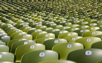 Eine Menge grüner Plastiksitzschalen mit Nummern darauf.