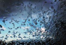 Sicht durch ein Dachfenster auf ein blaues Loch in einer dunklen Wolkenwand. Auf dem Dachfenster liegen Reste eines Hagelschauers.