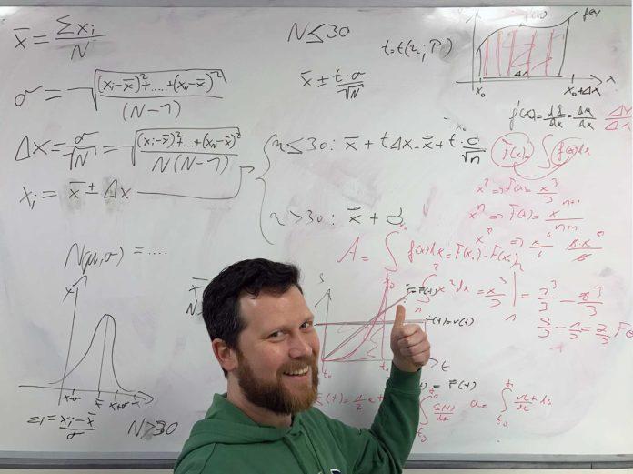 Johannes sitzt vor einem mit allerlei mathematischen Formeln beschriebenen Whiteboard.