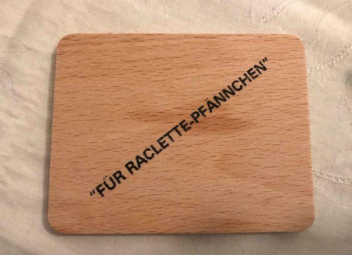 Ein kleines Holzbrett mit Fettflecken, darauf ist schräg in Anführungszeichen gedruckt: Für Raclette-Pfännchen