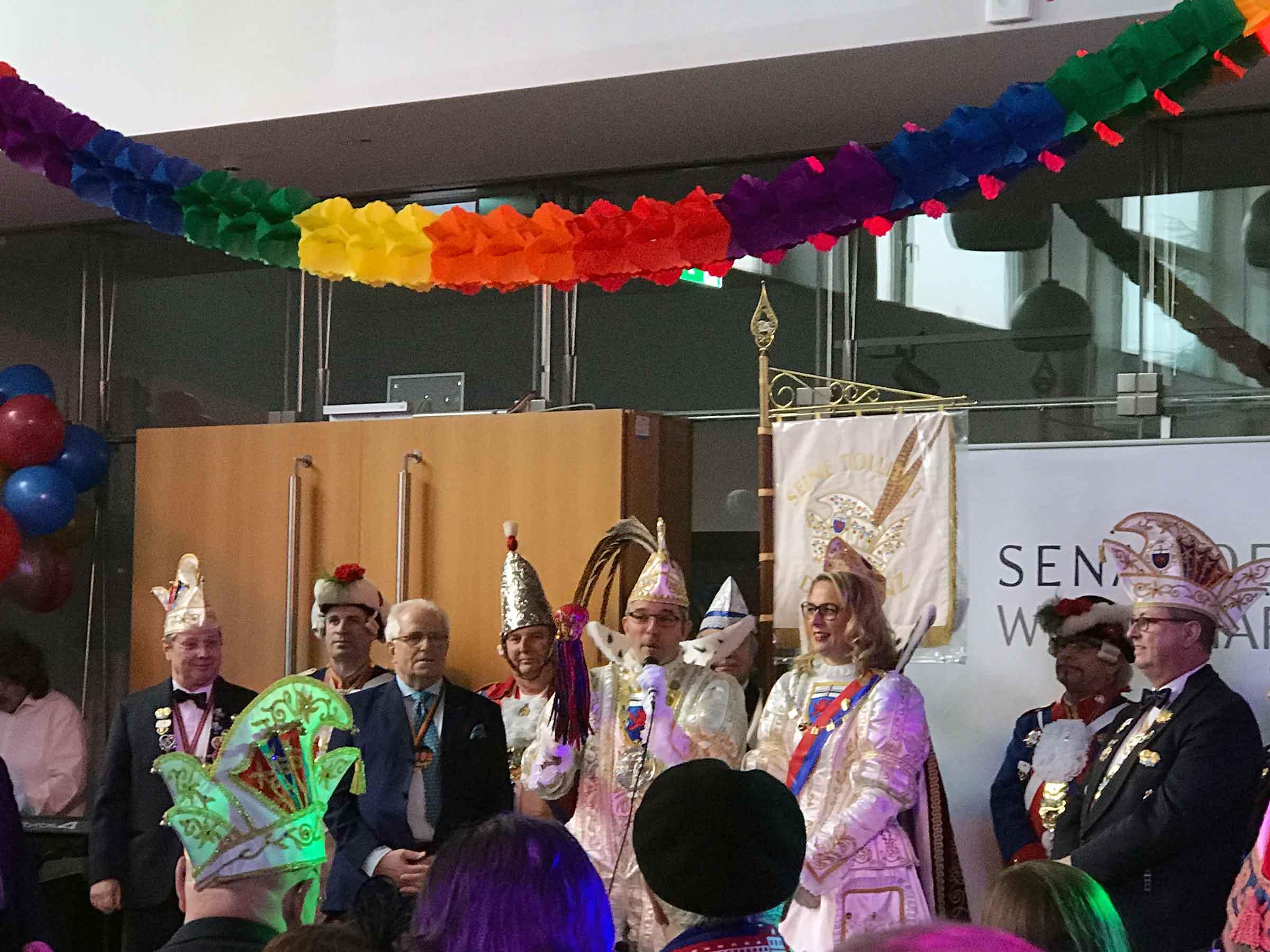 Viele Menschen stehen auf oder vor der Bühne, darüber eine bunte Girlande. Die Menschen auf der Bühne tragen karnevalistische Kopfbedeckungen. Der Prinz spricht in ein Mikrofon.