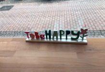 """Ein aus Holz geschnitzter und bunt angemalter Aufsteller, der sich """"To Be Happy"""" liest, dahinter eine Blume."""