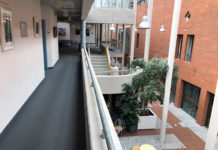 Der Blick auf von der Galerie des ersten Stocks, links eine Wand, rechts blickt man nach unten. Viel Beton und eine Ziegelwand.