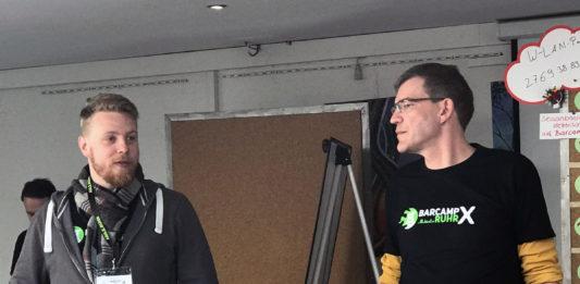 Zwei Männer stehen vor dem Publikum, der eine redet, der andere sieht ihn an