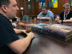 Mehrere Personen sitzen an einem großen Tisch. Auf dem Tisch liegen einige Kartons mit Brettspielen.