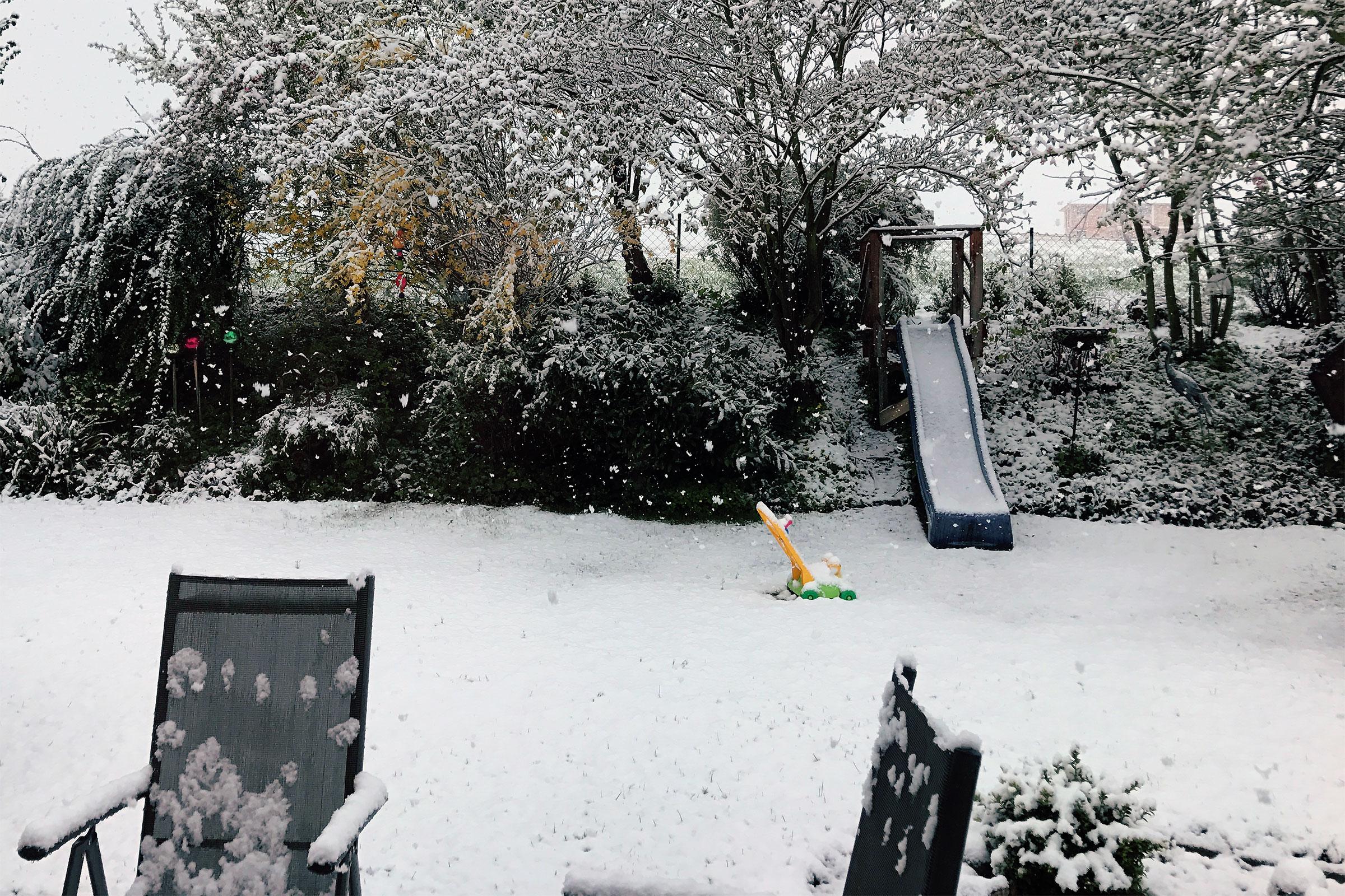Schnee im Garten, im Hintergrund eine Kinderrutsche, davor – eingeschneit – ein Kinderrasenmäher