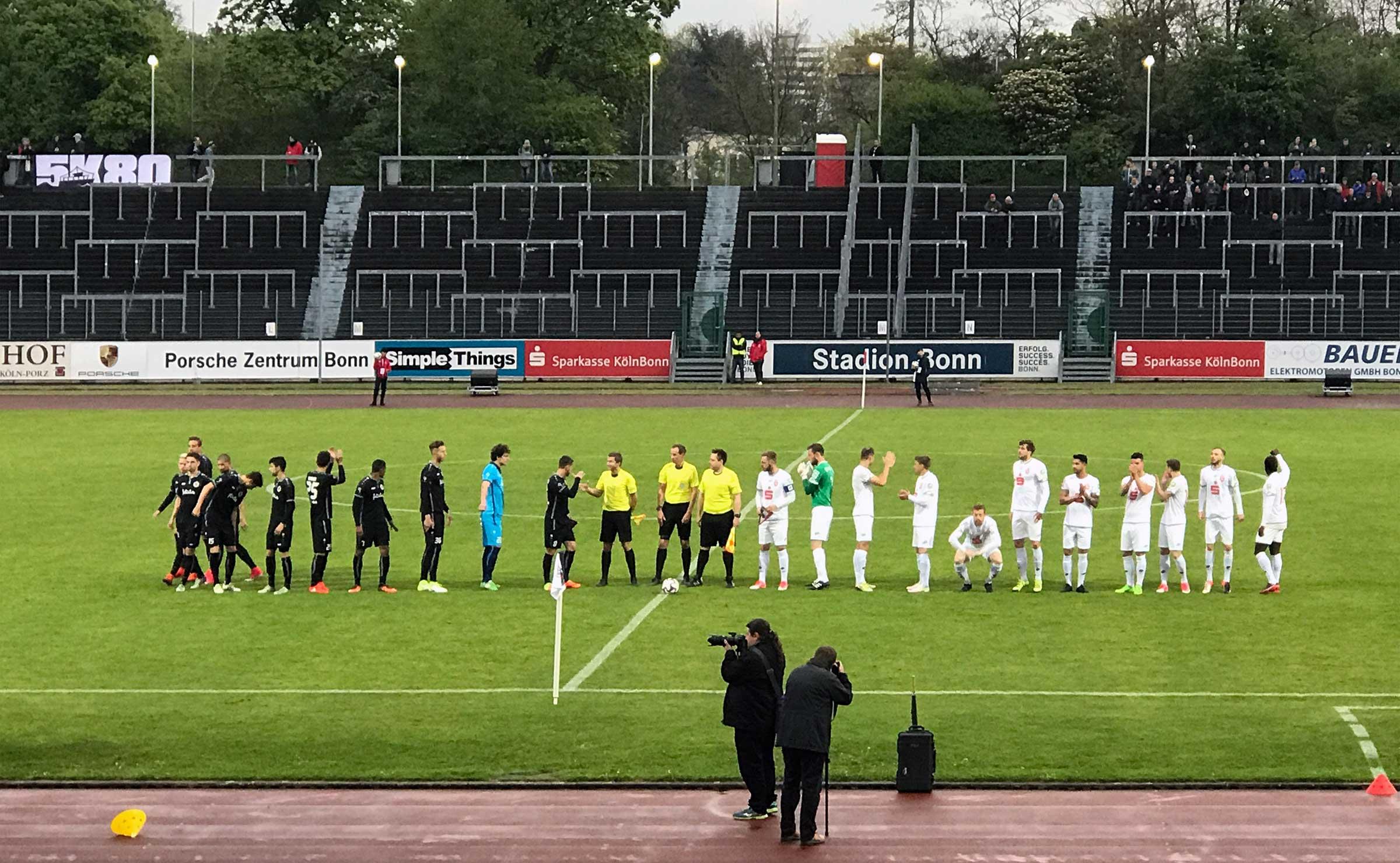 Eine dunkelblau und eine weiß gekleidete Fußballmannschaft steht in einer Reihe vor der Tribüne, in der Mitte die drei gelb-schwarz gekleideten Schiedsrichter.