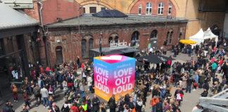 Viele Menschen im Außenbereich, im Hintergrund ein Gebäude in Ziegelbauweise. In der Mitte steht ein großer bunter Würfel mit dem Motto: Love out loud.
