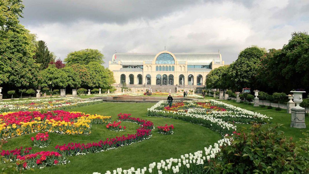 Im Hintergrund ein großes Gebäude, im Vordergrund schön gepflanzte Blumenarragangements.