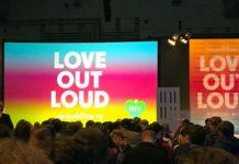 """Aus den hinteren Reihen eines großen dunklen Saals die Bühne mit einer bunten Leinwand, auf der """"Love out loud"""" steht, daneben ein gleich gestaltetes großes Plakat."""