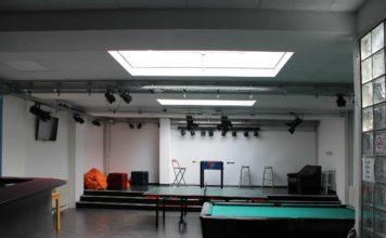 Ein Raum mit Oberlicht, im Vordergrund ein Billardtisch, dahinter eine Tischtennisplatte, dahinter auf einem Podest ein Kicker und ein braunes Ledersofa.