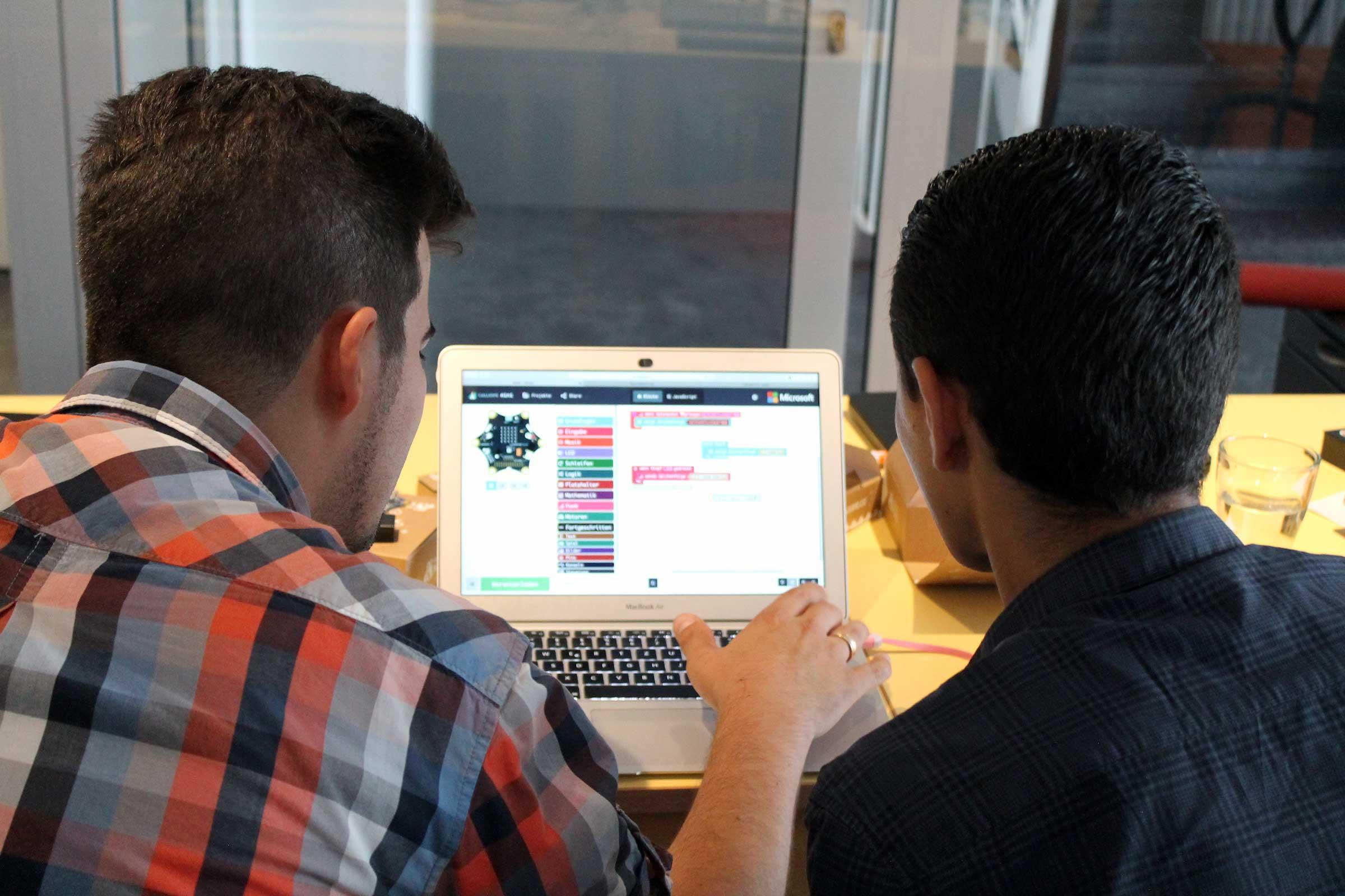 Ein Mann und ein Junge sehen auf einen Laptopbildschirm.