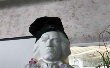 Eine typisch grimmig dreinsehende Beethovenstatue mit einer schwarzen Kochmütze aufgezogen, auf der der Coppeneur-Schriftzug gedruckt ist.