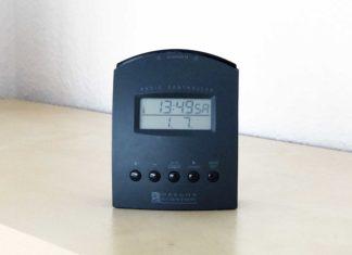 Ein beinahe quadratisches Gerät, ca. 10 cm Kantenlänge. Im oberen Drittel ein Quarz-Display mit Uhrzeit, Tag und Datum, darunter fünf Knöpfe. Die obere Kante ist leicht nach außen gewölbt und funktioniert als Schalter.