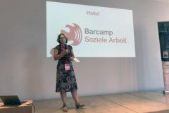 Eine Frau im Kleid steht auf der Bühne, sie spricht in ein Mikrofon. Hinter ihr wird das Logo des Barcamps an die Wand projiziert.