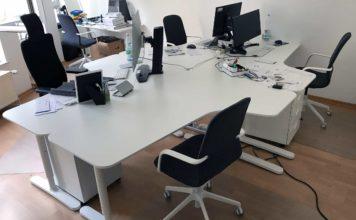 Vier weiße Schreibtische sind zu einer Insel angeordnet, auf dreien davon stehen Bildschirme und andere Sachen. Im Hintergrund noch ein weiterer kleiner Tisch.
