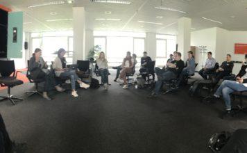 Mehrere Menschen sitzen auf Stühlen in einer kreisförmigen Anordnung, viele sehen auf ihr Handy. Links ist ein großer Bildschirm mit App-Symbolen an der Wand.