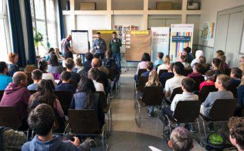 Ein Saal von hinten, darin viele Jugendliche auf Stühlen. Sie sehen zwei Männern mit Mikrofonen zu.