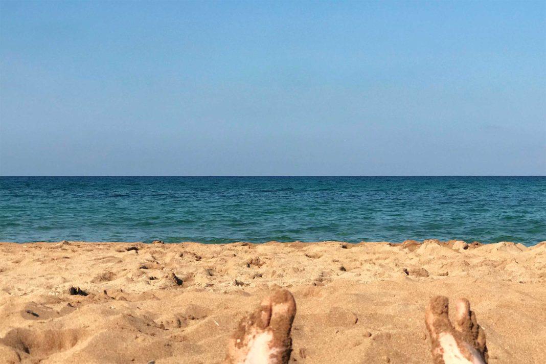 Strand, Meer und zwei teilweise mit Sand bedeckte Füße