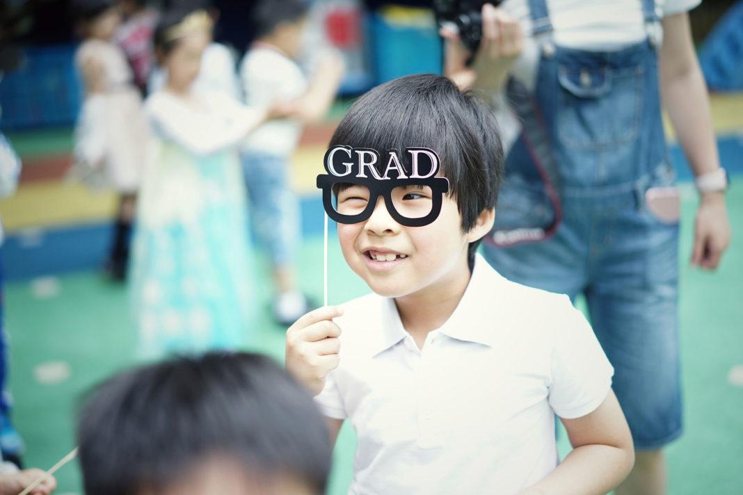 Ein kleiner Junge hält sich eine Brille mit Stil vor die Augen, auf dem Brillenrand stehen die vier Buchstaben GRAD.