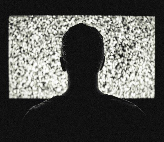 Der Schattenriss eines Manns vor einem Fernseher, der nur Rauschen zeigt.