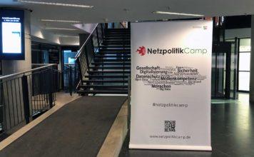 Ein großes Rollup mit Logo des Netzpolitikcamps und einer Wordcloud darunter, auf der NRW-Orte und Netzpolitikbegriffe stehen. Daneben ein Aufgang und eine Treppe.