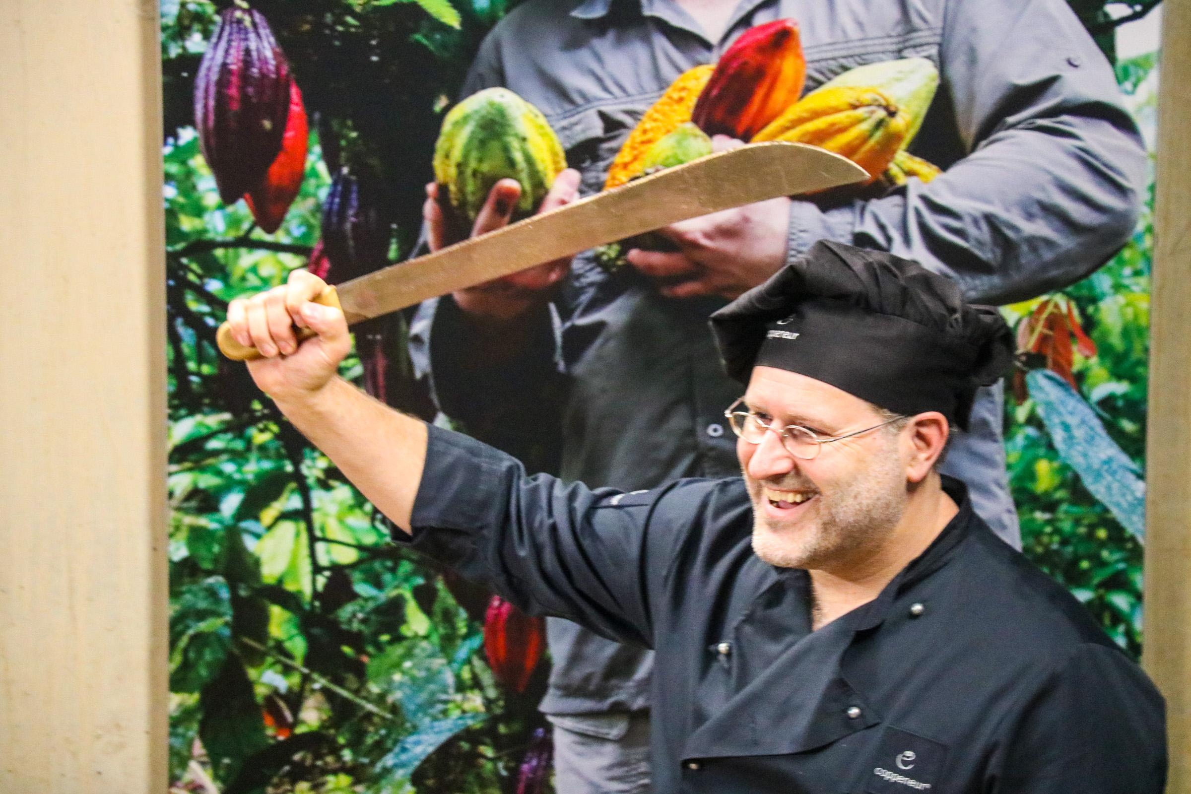Ein Mann mit schwarzer Kochmütze hält schräg über seinen Kopf eine Machete. Er lacht.