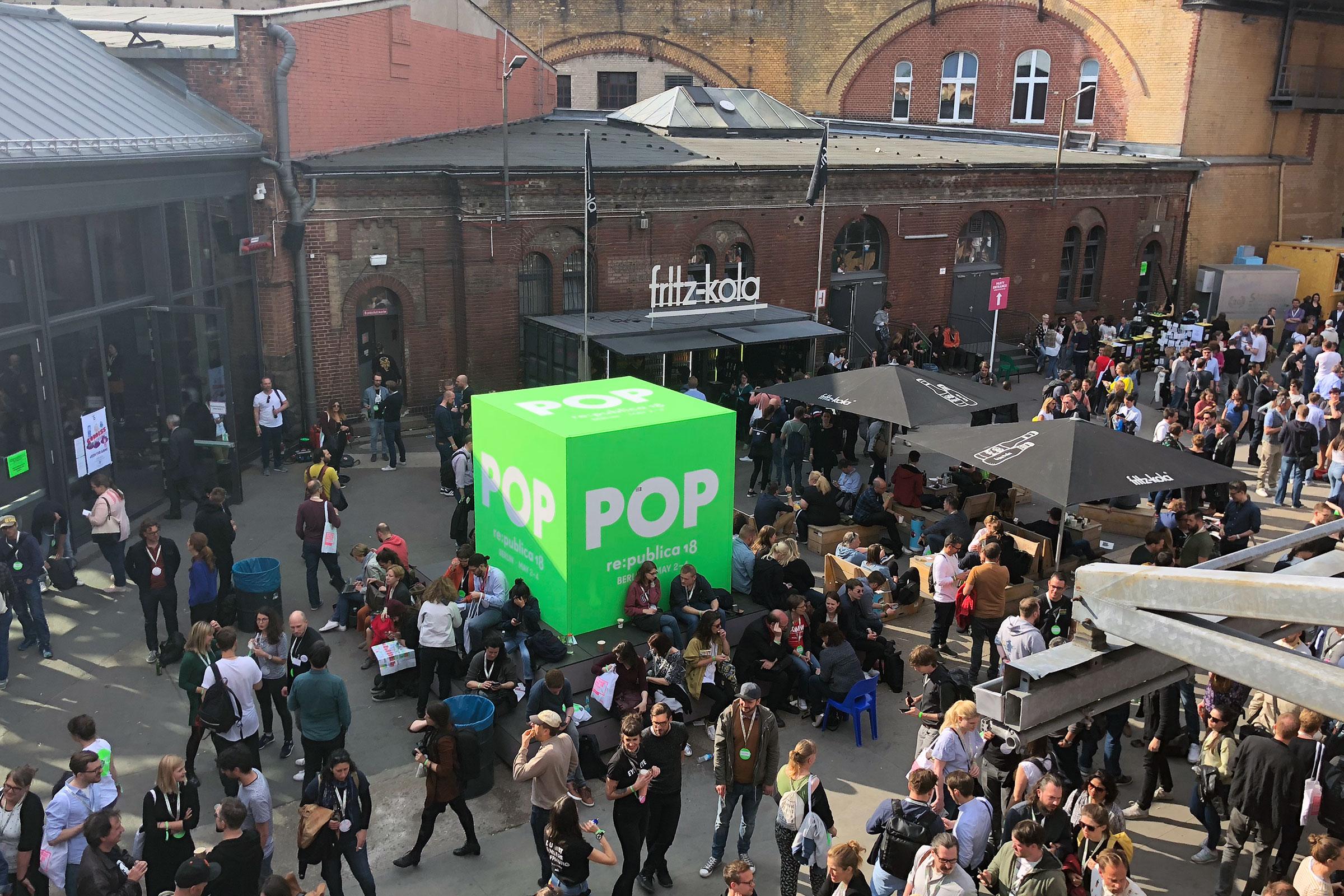 Viele Menschen stehen herum, in der Mitte ein großer grüner Würfel mit der Aufschrift POP.
