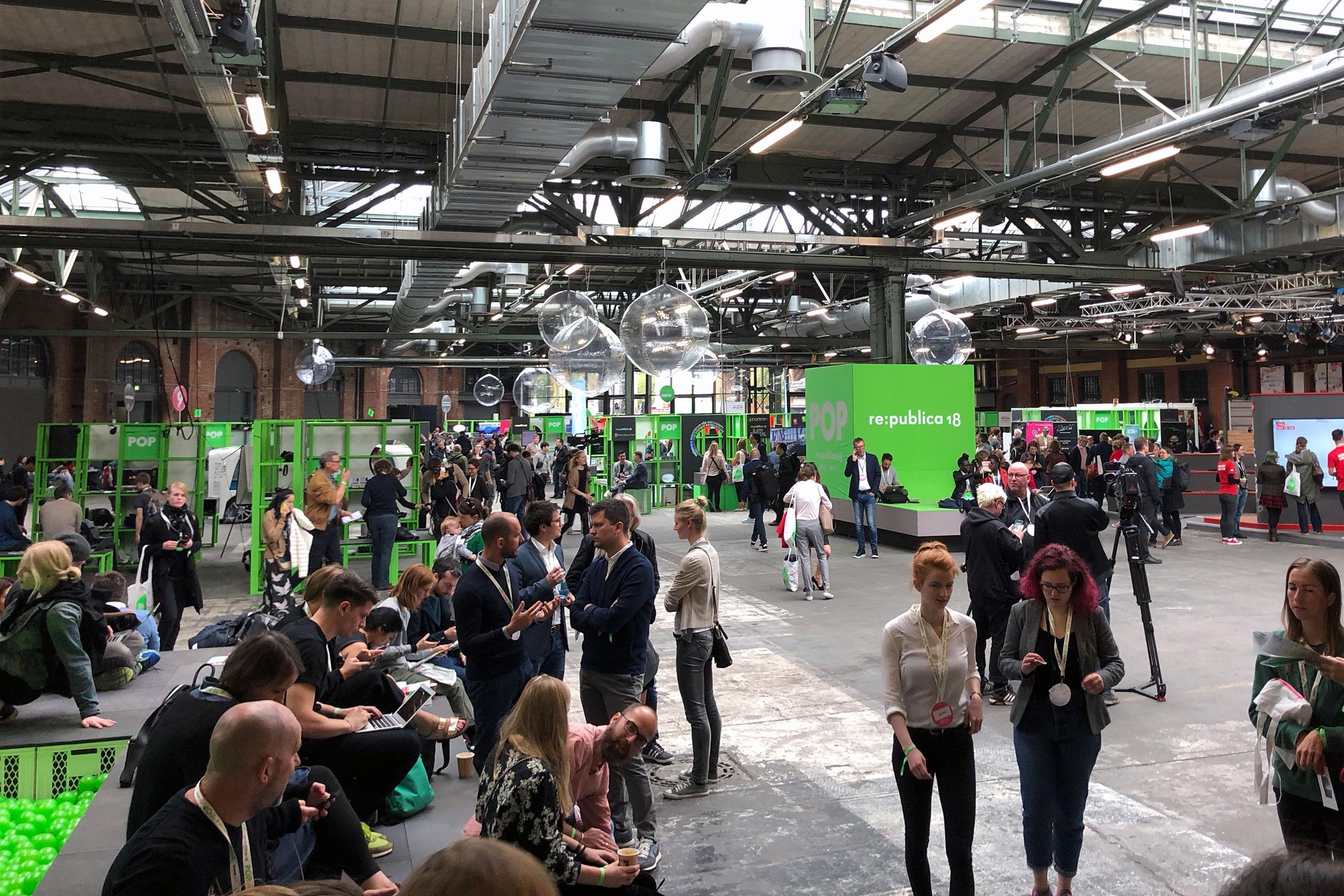 Viele Menschen in einer Halle, im Hintergrund ein grüner Würfel.