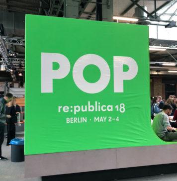 """Ein großer grüner Würfel mit der Aufschrift POP, darunter """"re:publica 2018, Berlin, May 2-4"""". Daneben am Würfel angelehnt sitzt ein Mann mit Laptop auf dem Schoß."""