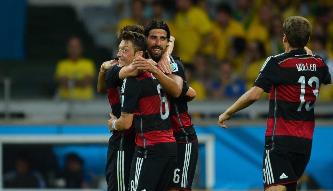 Zwei Fußballspiler umarmen den lachenden Özil, mit Rücken zum Bild steht außerdem Müller.