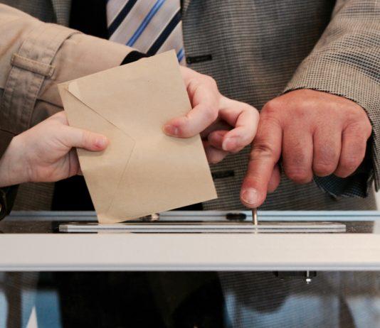 Zwei Hände halten einen Brief über den Einwurfschlitz einer Wahlurne. Dahinter zeigt eine Hand auf den Schlitz.
