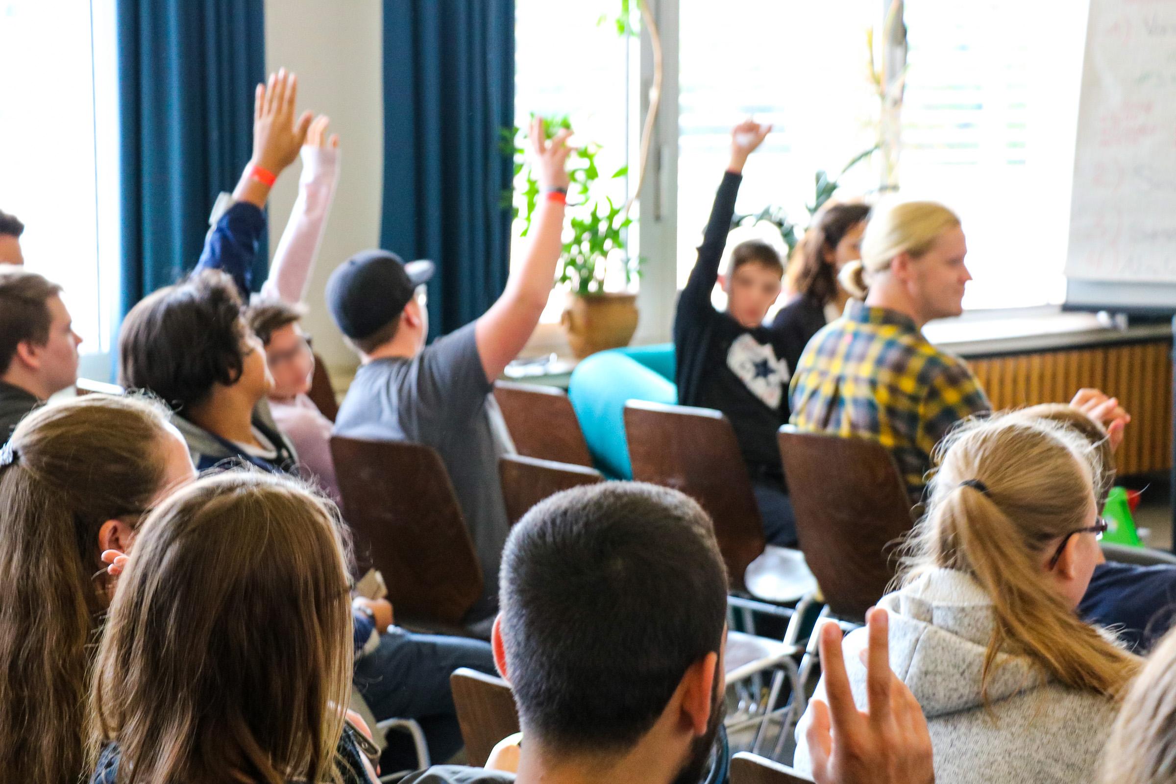 Einige Jugendliche, ein paar heben ihren Arm, um Interesse an einer Session zu signalisieren.