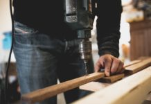 Ein Mann bohrt mit einer Bohrmaschine ein Loch in eine Holzlatte.