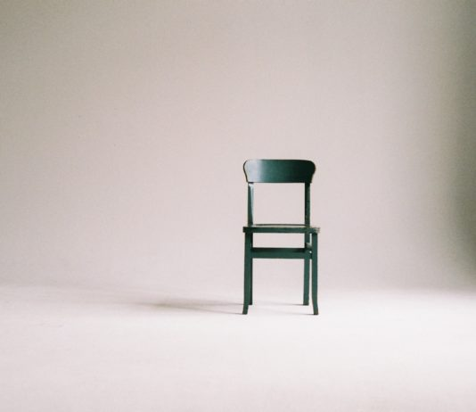 Ein grüner Stuhl vor einem weißen Hintergrund.