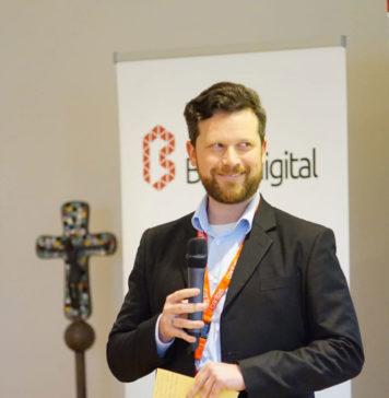 Ich stehe da mit Mikrofon in der Hand und lächle schief. Hinter mir ein Kreuz und zwei Roll-ups von Bonn.digital und der Caritas.