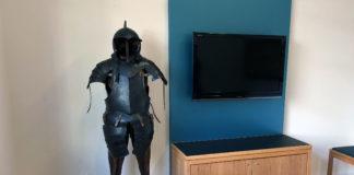Eine Ritterrüstung steht neben einem Fernseher, der an die Wand geschraubt ist.